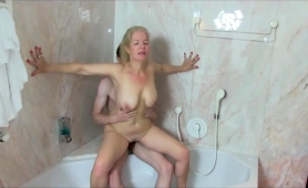 buxom-blonde-milf-sucks-and-fucks-a-young-cock-in-the-shower
